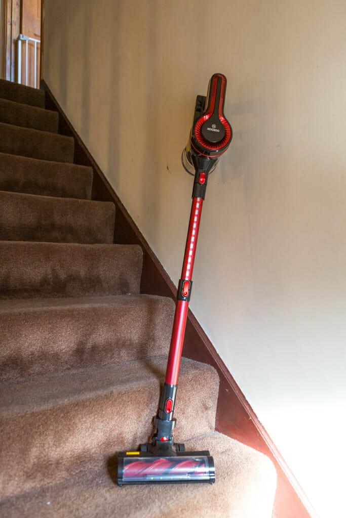 The Moosoo K17U 4 in 1 Handheld Cordless Vacuum leaning on some stairs.