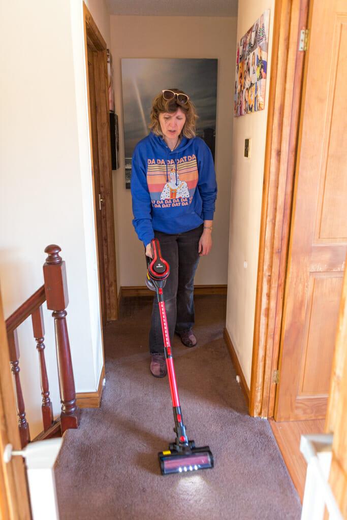 The Moosoo K17U 4 in 1 Handheld Cordless Vacuum being used by a woman to clean her landing.