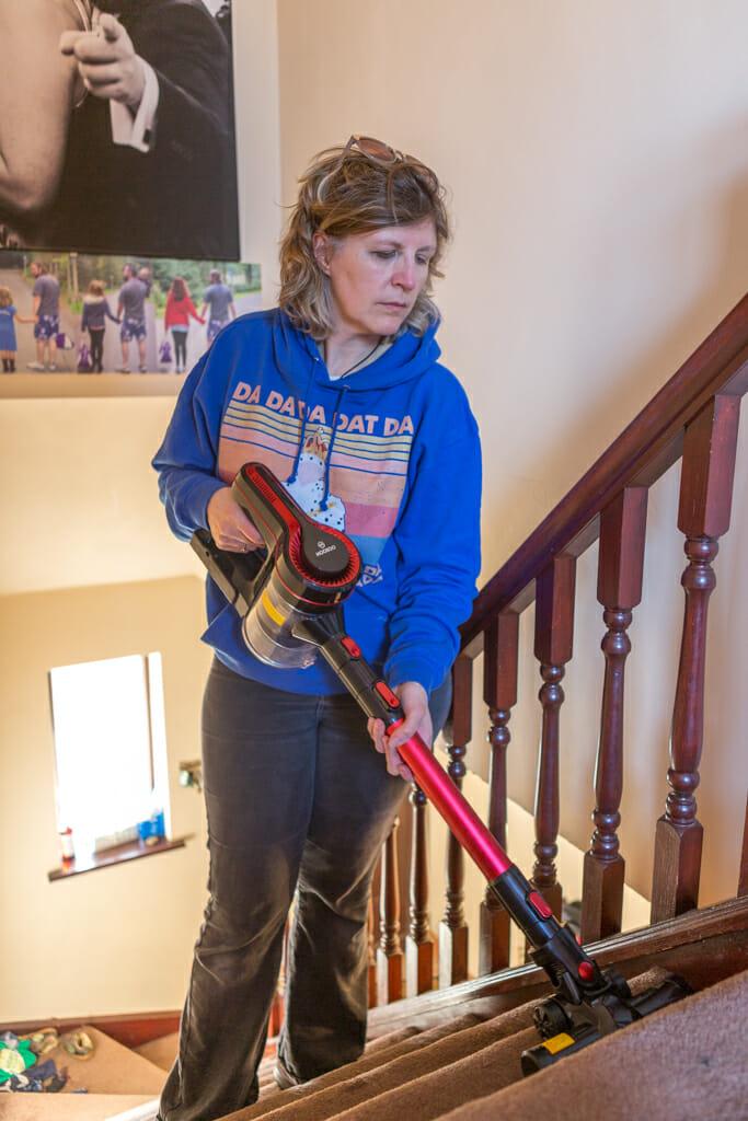A woman using the Moosoo K17U 4 in 1 Handheld Cordless Vacuum to clean some stairs.